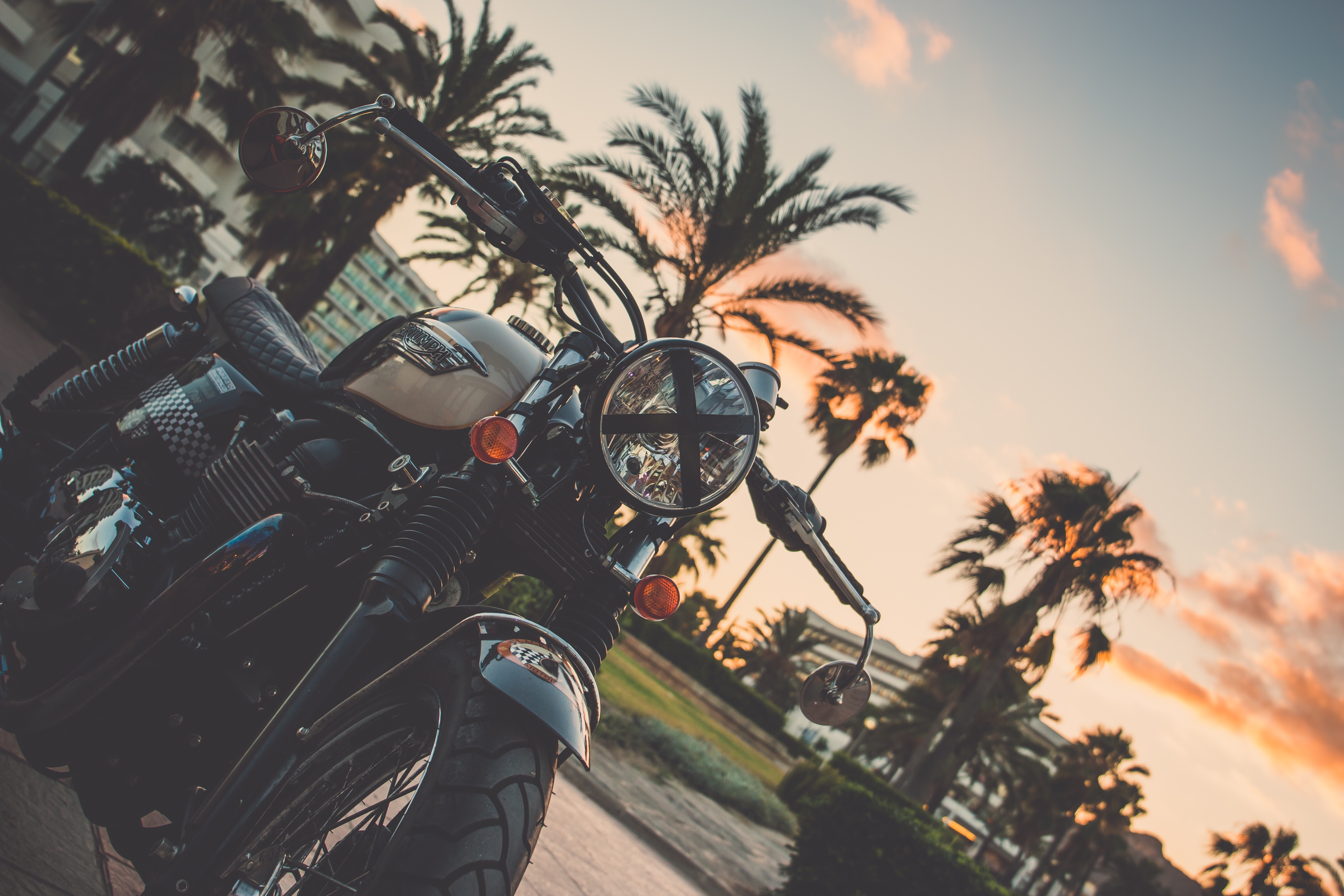 Motorcycle with palm trees and a setting sun