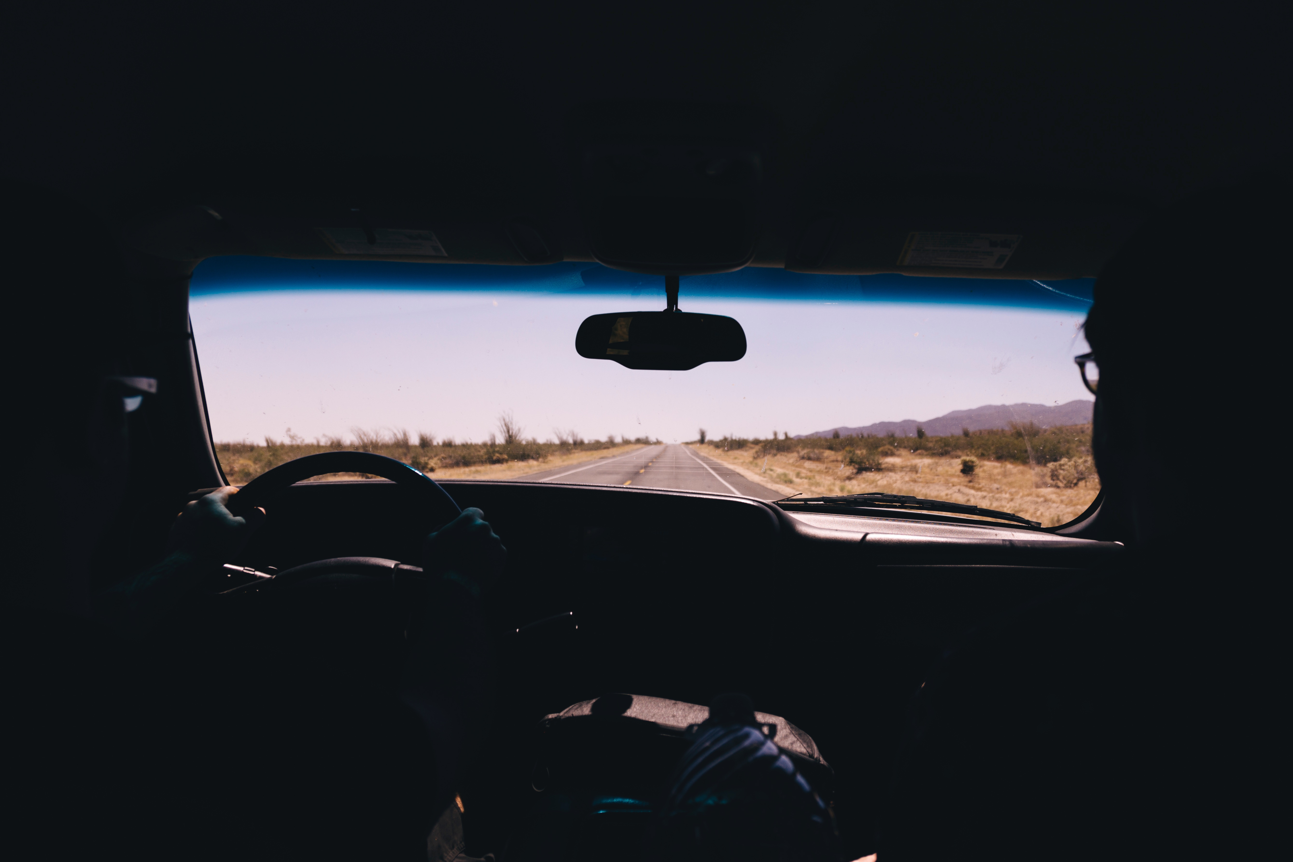 Picture taken from the backseat of car looking out a long road