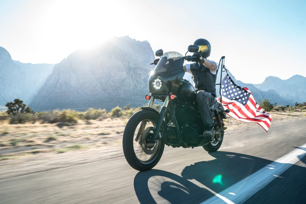 Man riding motorcycle with American flag
